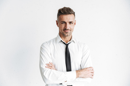 Handsome confident businessman wearing formal clothes standing isolated over white background, arms folded
