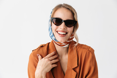 Image of a laughing beautiful young woman wearing silk stylish scarf posing isolated over white wall background wearing sunglasses.