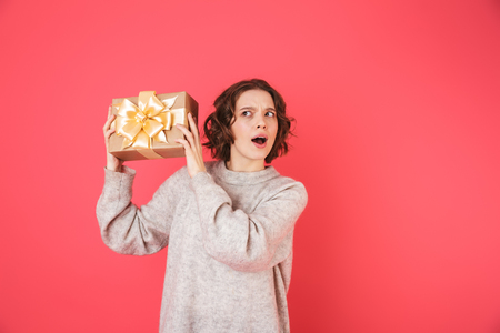Portrait of a cheerful young woman standing isolated over pink background, holding present box Stok Fotoğraf