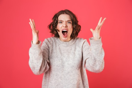 Portrait of a shocked young woman standing isolated over pink background, screaming Stock Photo