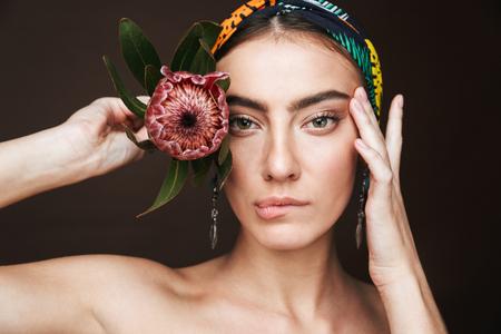 Schönheitsporträt einer jungen schönen Frau mit Stirnband und Ohrringen, die isoliert auf schwarzem Hintergrund steht