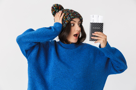 Portrait of cheerful woman 30s wearing winter hat holding holding passport and travel tickets while standing isolated over white background
