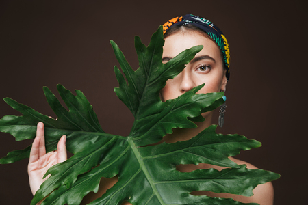 Beauty portrait of a topless young beautiful woman wearing headband and earrings standing isolated over black background, posing with green tropical leaf Stok Fotoğraf