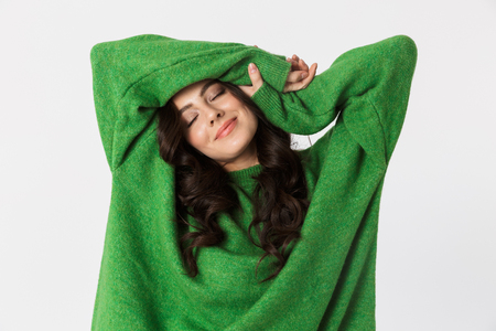 Image of beautiful young woman dressed in green sweater posing isolated over white wall background. 免版税图像 - 118797685