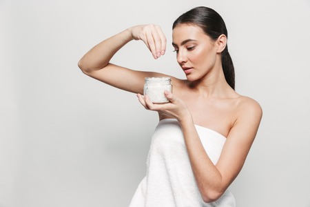Beauty portrait of a young healthy attractive brunette woman standing isolated over white background, holding jar of spa salt