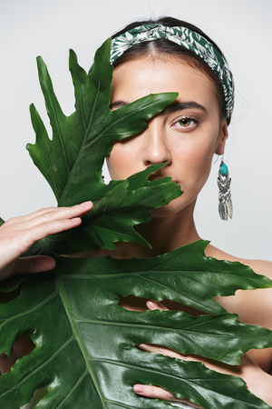 Beauty portrait of a topless young beautiful woman wearing headband and earrings standing isolated over white background, posing with green tropical leaf