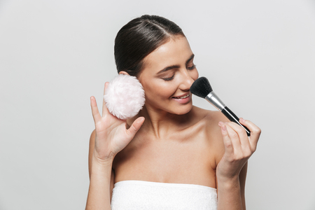 Beauty portrait of a pretty young woman wrapped in towel standing isolated over white background, holding powder puff and a makeup brush