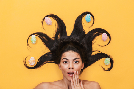 Image of beautiful shocked young woman lies isolated on yellow background over easter eggs.