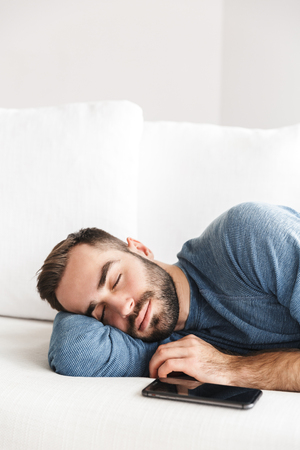 Attractive young man relaxing on a couch at home, sleeping with mobile phone