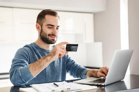Glücklicher, gutaussehender Mann, der am Küchentisch sitzt, am Laptop arbeitet und Kreditkarte verwendet Standard-Bild