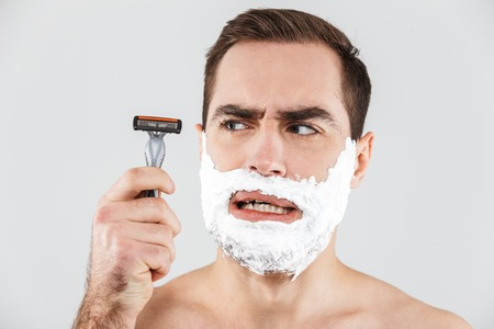 Portrait of a cheerful shirtless bearded man standing isolated over white background, face covered with shaving foam, holding a razor