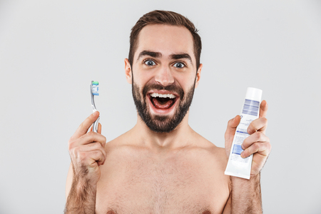 Close up portrait of a handsome bearded man standing isolated over white background, showing toothpaste and toothbrush