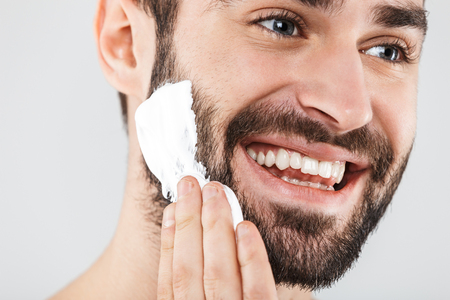 Close up portrait of a handsome bearded man standing isolated over white background, applying shaving foam 版權商用圖片