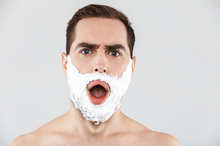 Close up portrait of a handsome bearded man with shaving foam on his face standing isolated over white background