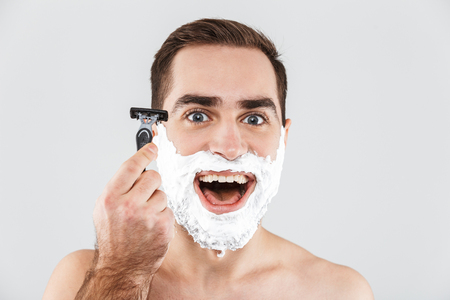 Close up portrait of a handsome bearded man with shaving foam on his face standing isolated over white background, ready to shave