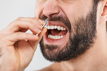 Close up portrait of a suffering bearded man standing isolated over white background, plucking out his nose hair Stock Photo