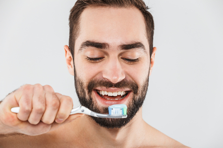 Close up portrait of a handsome bearded man standing isolated over white background, brushing his teeth