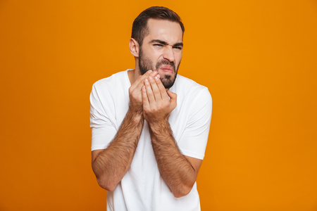 Image of european man 30s in t-shirt touching his cheek and suffering from toothache while isolated over yellow background 版權商用圖片