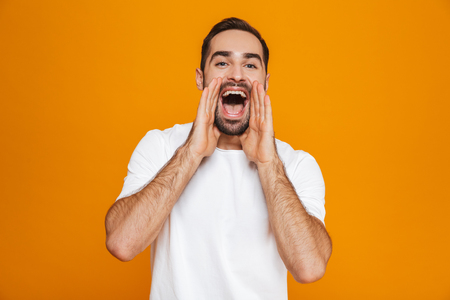Image of attractive man 30s in t-shirt while calling or screaming while standing isolated over yellow background Imagens