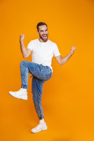 Full length image of ecstatic guy 30s in t-shirt and jeans laughing and rejoicing while standing isolated over yellow background