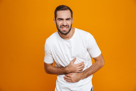 Image of caucasian man 30s in t-shirt bending and touching his belly because of pain while isolated over yellow background