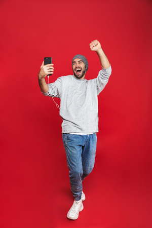 Full length photo of european man 30s singing while listening to music with earphones and mobile phone isolated over red background Stok Fotoğraf - 118814052