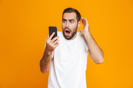 Photo of terrified man 30s in casual wear looking at mobile phone with fear isolated over yellow background Stock Photo