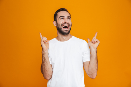 Image of unshaved man 30s in t-shirt pointing finger upward while standing isolated over yellow background