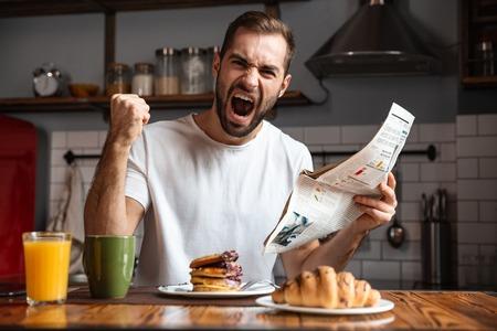 Angry shocked man having breakfast, reading newspaper