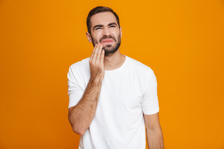 Image of unshaved man 30s in t-shirt touching his cheek and suffering from toothache while isolated over yellow background