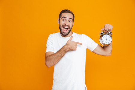 Photo of brunette man 30s in casual wear holding alarm clock isolated over yellow background Stock Photo