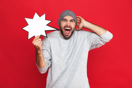 Image of bearded man 30s wearing hat holding blank idea poster isolated over red background Imagens - 118814258