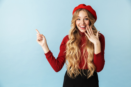 Portrait of cheerful blond woman 20s wearing red beret smiling while standing isolated over blue background in studio