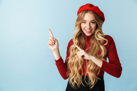 Portrait of charming blond woman 20s wearing red beret pointing fingers upward while standing isolated over blue background in studio