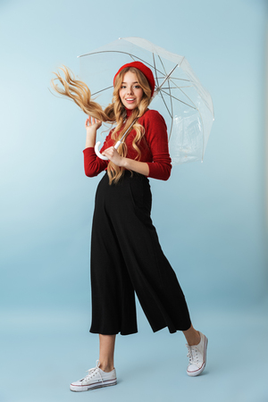 Full length portrait of optimistic blond woman 20s with long hair walking under umbrella while isolated over blue background in studio