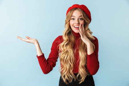 Image of gorgeous blond woman 20s wearing red beret smiling and holding copyspace on palm while standing isolated over blue background in studio