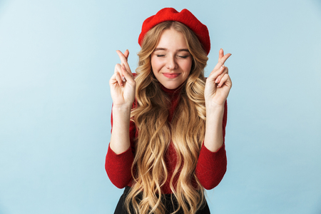 Image of nice blond woman 20s wearing red beret keeping fingers crossed while standing isolated over blue background in studio