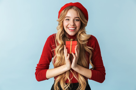 Image of trendy blond woman 20s wearing red beret holding present box isolated over blue background in studio 写真素材