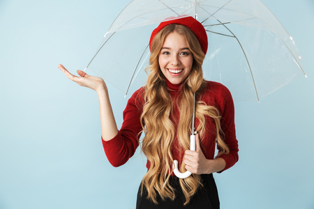 Portrait of charming blond woman 20s with long hair standing under umbrella while isolated over blue background in studio 写真素材
