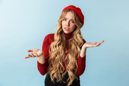 Portrait of discontent blond woman 20s wearing red beret throwing up hands while standing isolated over blue background in studio