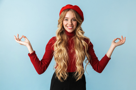 Portrait of happy blond woman 20s wearing red beret showing zen and meditation gesture while standing isolated over blue background in studio 写真素材