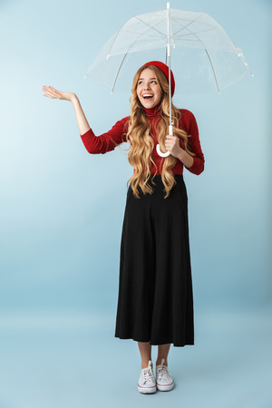 Full length portrait of gorgeous blond woman 20s with long hair walking under umbrella while isolated over blue background in studio 写真素材