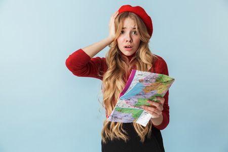 Image of concerned blond woman 20s wearing red beret holding world map isolated over blue background in studio