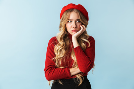 Image of discontent blond woman 20s wearing red beret looking aside while standing isolated over blue background in studio 写真素材