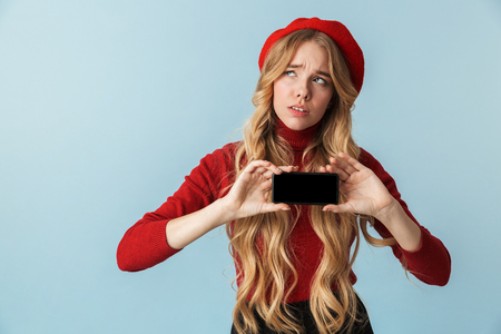 Photo of european girl 20s wearing red beret using mobile phone isolated over blue background in studio