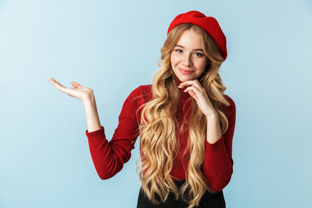 Image of caucasian blond woman 20s wearing red beret smiling and holding copyspace on palm while standing isolated over blue background in studio 写真素材