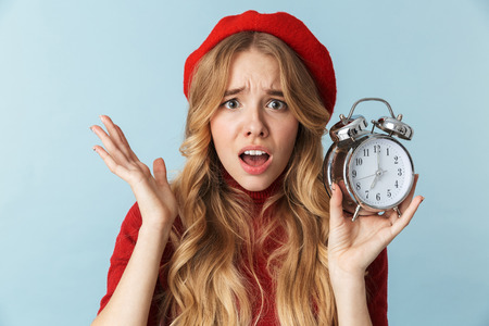 Image of confused blond woman 20s wearing red beret holding alarm clock isolated over blue background in studio
