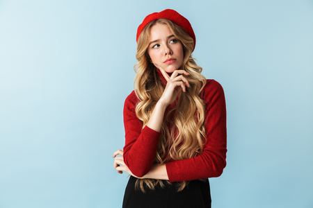 Portrait of stylish blond woman 20s wearing red beret looking aside while standing isolated over blue background in studio