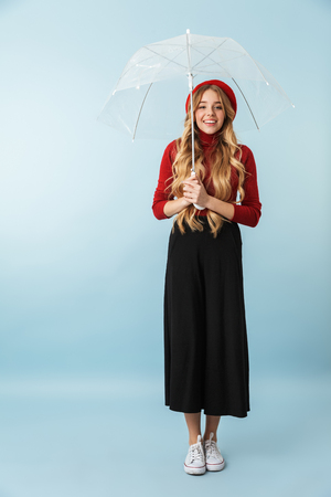 Full length portrait of european blond woman 20s with long hair walking under umbrella while isolated over blue background in studio