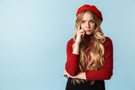 Portrait of offended blond woman 20s wearing red beret looking aside while standing isolated over blue background in studio 写真素材